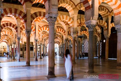 Woman walking through the arches of the Mezquita of Cordoba, Spain