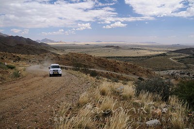 White bakkie (pick-up truck) driving up a steep gravel road mountain pass road, flat desert in the background, elevated view