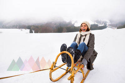Laughing senior woman sitting on sledge in snow-covered landscape