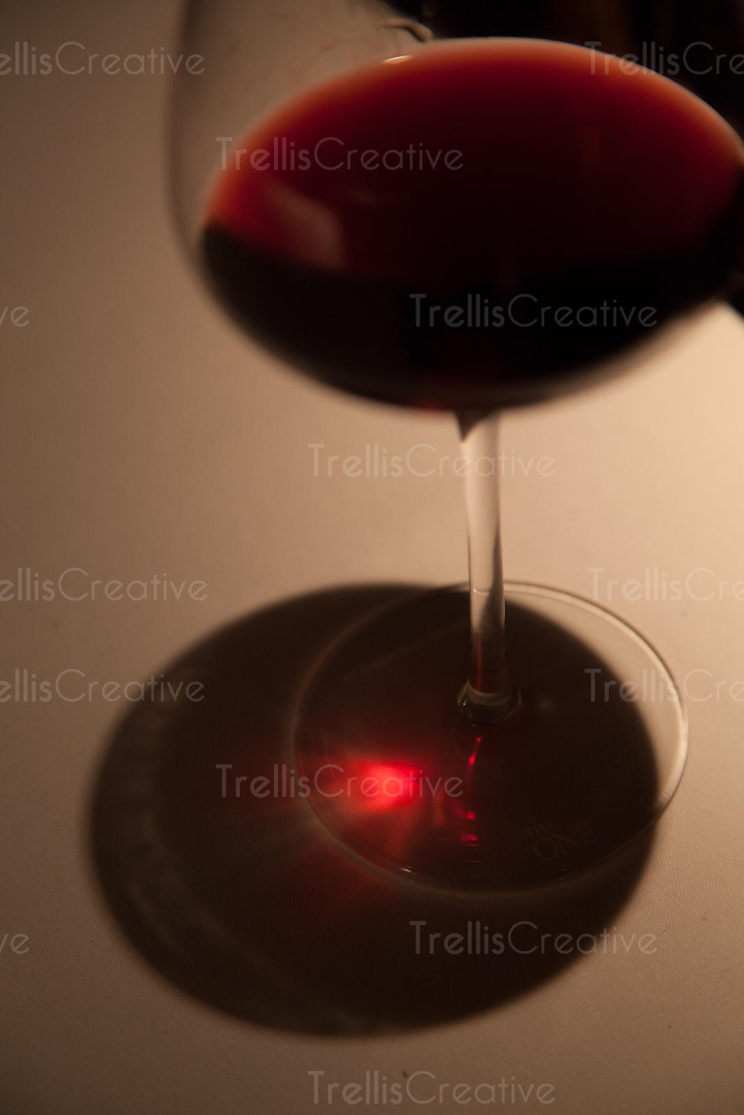 Glass of red wine on a white table with light shining through