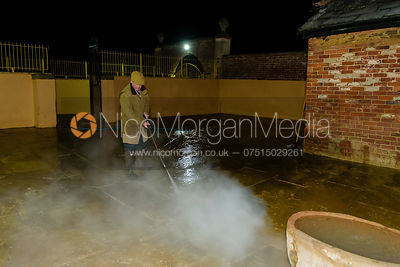 Huntsman John Holliday pressure washes the hound runs at the Belvoir Kennels
