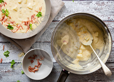 Potato and leek soup in a bowl and saucepan.
