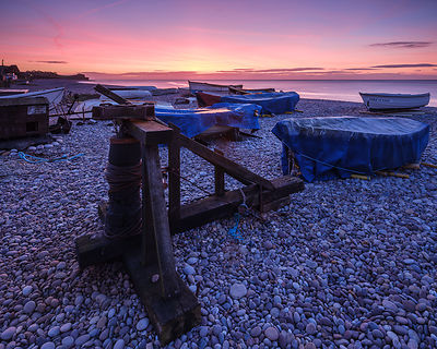 Capstan and boats on the pebbled beach at Budliegh Salterton, Devon, UK