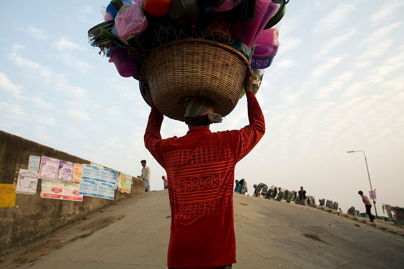 Bangladesh - Chittagong - A man carrying a bowl of clothes on his head walks up a steep slope on the southern shore of the Ka...