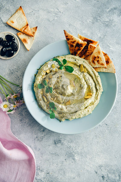 Creamy white bean hummus topped with herbs, olive oil and pistachios served in a light blue bowl with pita chips on the side....