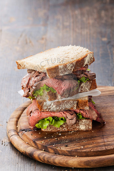 Roast beef sandwiches with lettuce on wooden cutting board on dark wooden background