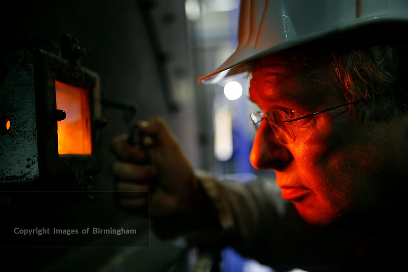 Furnace burning wood chippings to generate electricity. Man inspecting furnace through viewing window.