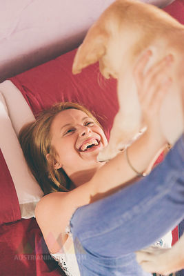 Happy young woman lying on bed playing with her Labrador Retriever puppy