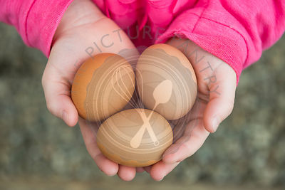 A child holding a handful of fresh eggs