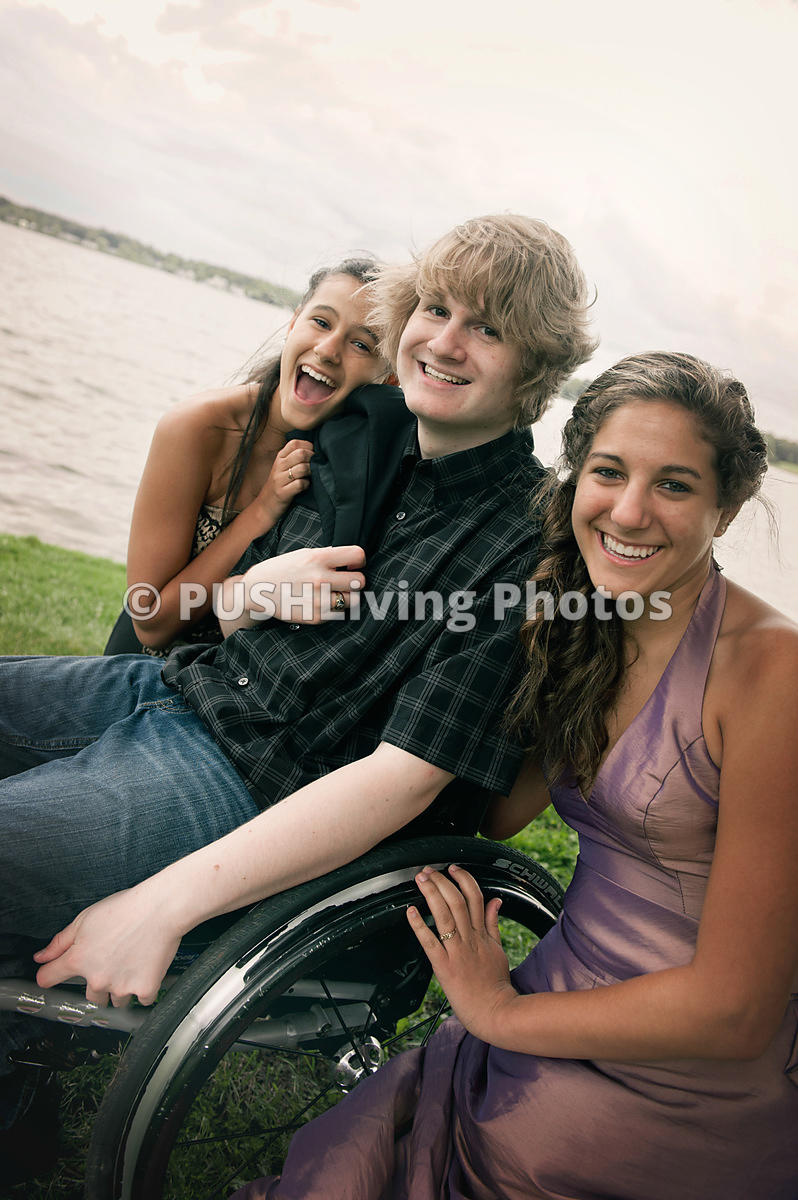 Young man in wheelchair with two beautiful young woman for an afternoon by the lake
