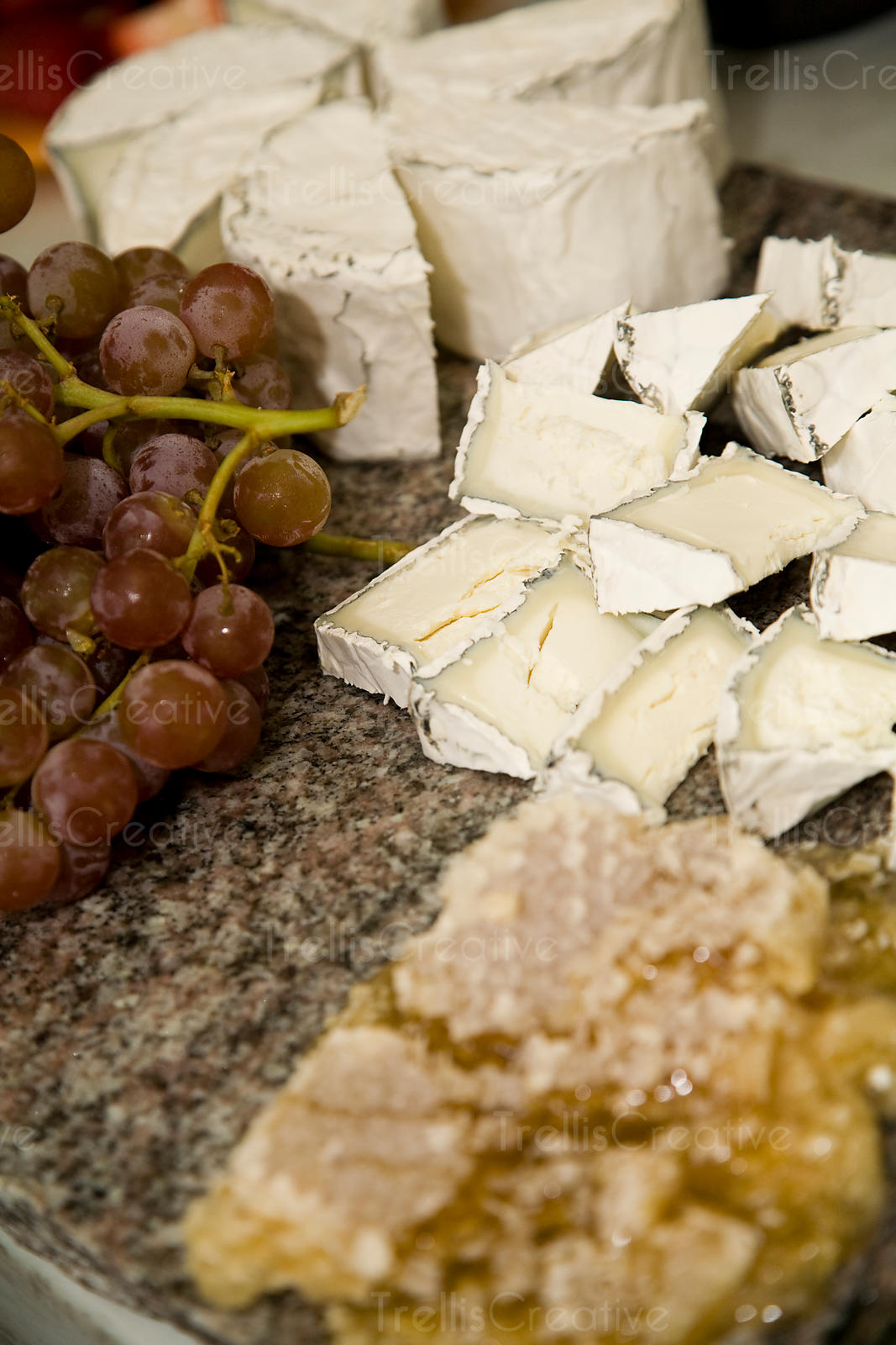 A cheese platter with grapes and honey