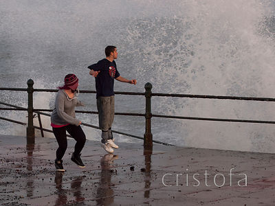 stiff breeze and a high tide cause waves to splash on Penzance Promenade