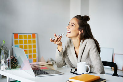 Happy young woman using smartphone at desk