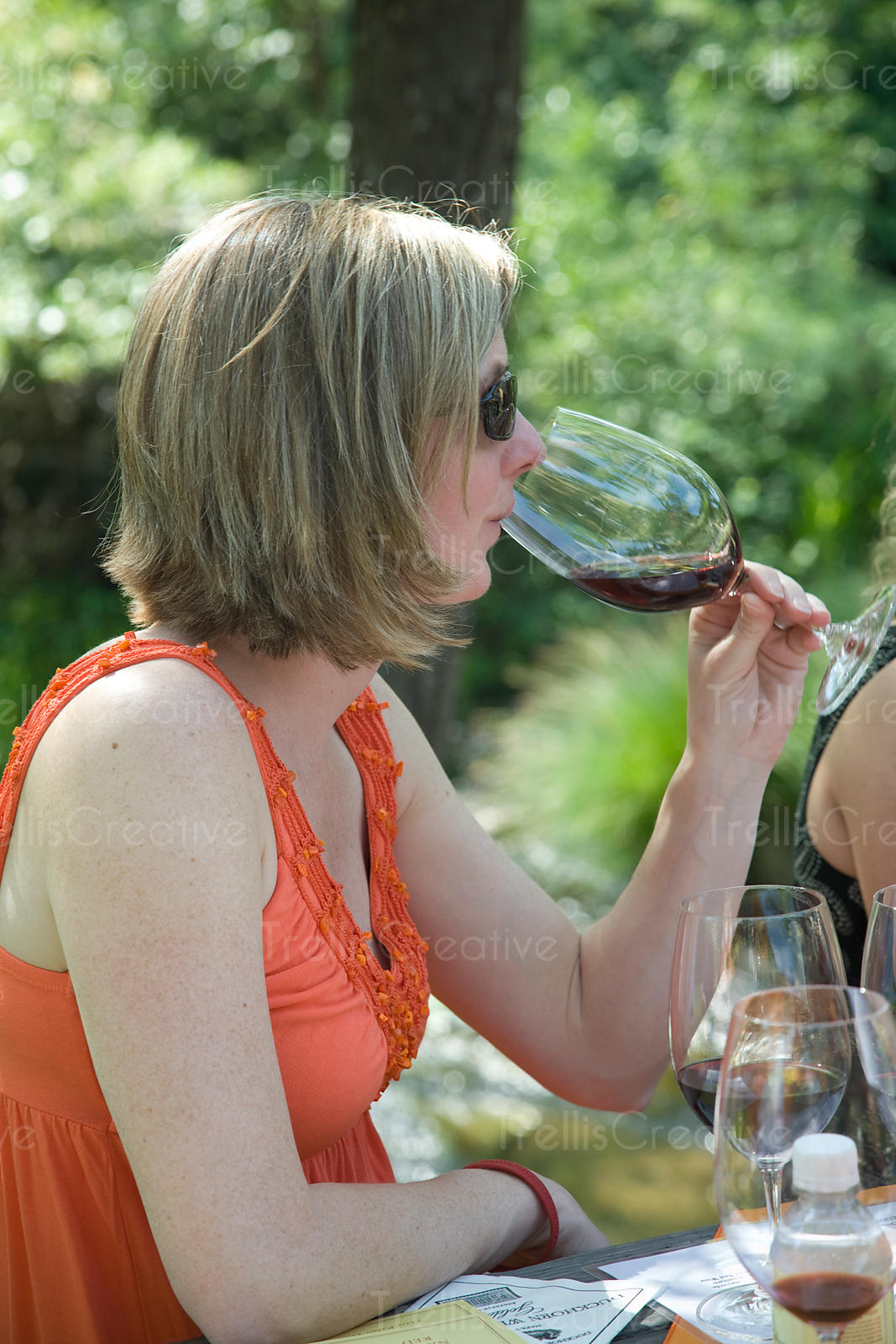 A young woman drinking a glass of red wine