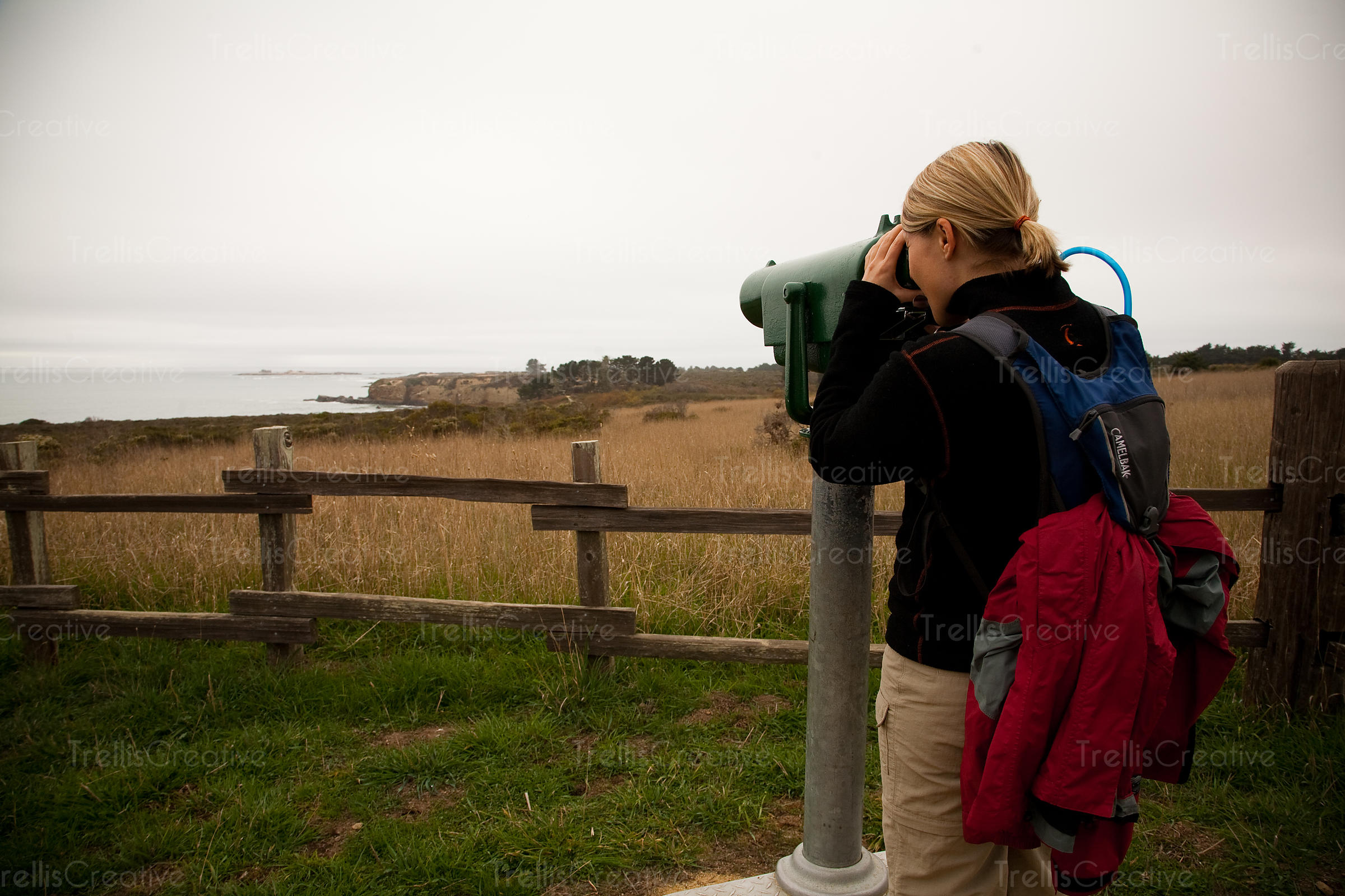 Close-up of a woman exploring the Ano Nuevo State Reserve by looking through telescope