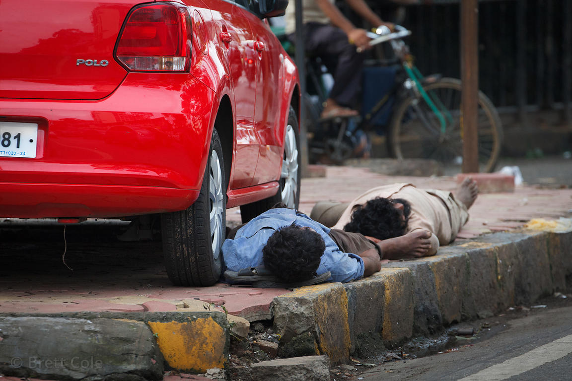 Men sleep on the side of the road in Mahim Mumbai, India.
