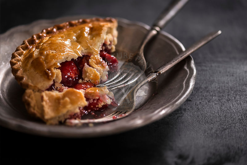 Small cherry pie on metal plate with antique forks. Dark, moody setting.