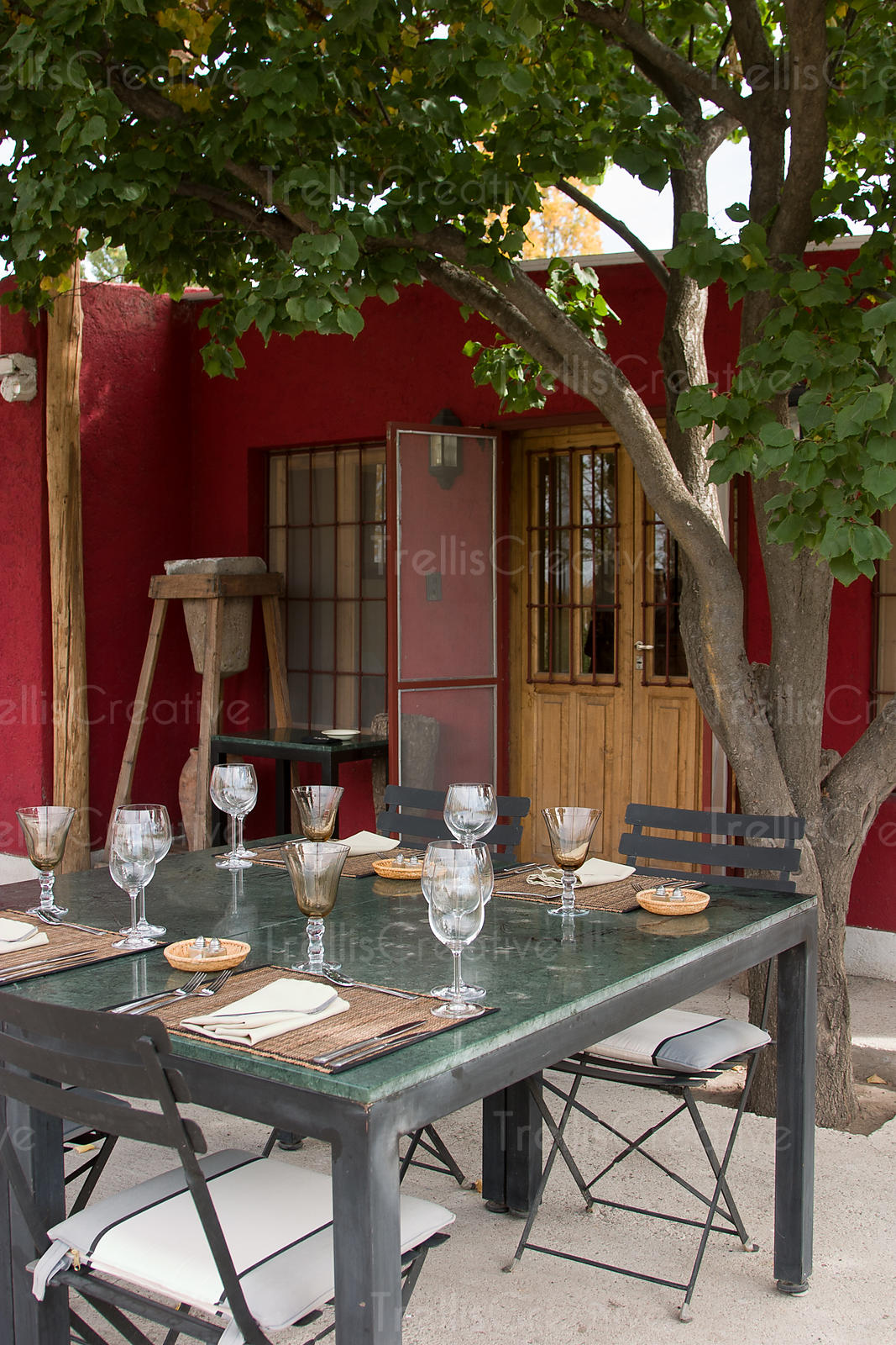 Table set for four in patio with shade tree. Red wall background, double wooden doors.