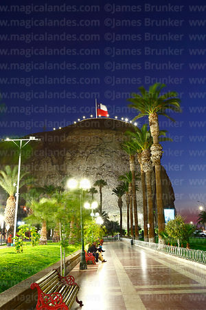 View of El Morro headland from Plaza Vicuña Mackenna at twilight, Arica, Region XV, Chile