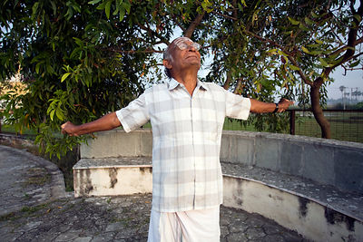 India - Cuddalore - An elderly resident stretches and takes the morning air at dawn by the lake at the Tamaraikulam Elders' V...