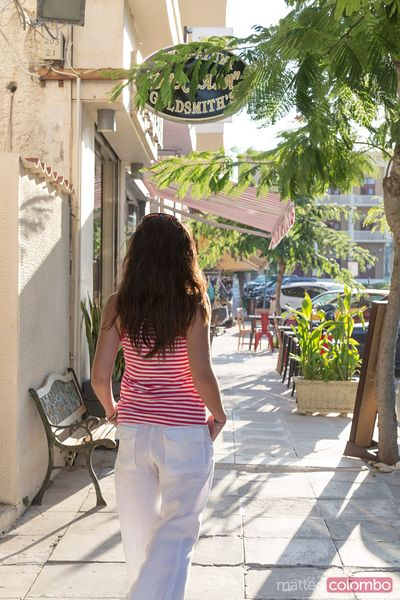 Woman walking in a small greek town in summer at sunset. Kefalonia, Greek Islands, Greece