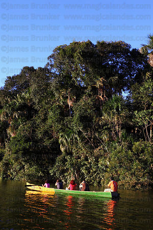 Hispanic family taking a trip in dugout canoe on Lake Chalalan , Madidi National Park , Bolivia
