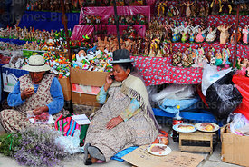 Aymara lady or cholita chatting on mobile phone during lunch break in in Christmas market, La Paz, Bolivia