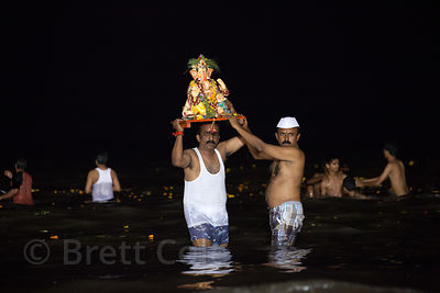 Families immerse idols of Ganesh into the Arabian Sea at Chowpatty Beach at night during the Ganesh Chaturthi festival in Mum...