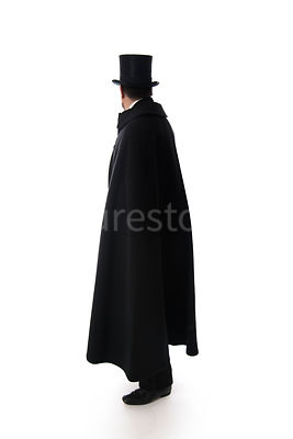A Victorian man in a hat and cloak looking away, in semi-silhouette – shot from eye level.