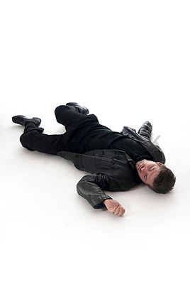 A Figurestock image of a man, laying dead on the floor – shot from eye level.