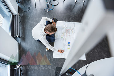 Businessman sitting on the floor of his office working at construction plan, top view