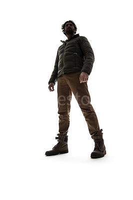A man in outdoor clothing, in semi-silhouette – shot from low level.