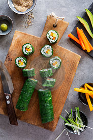 Vegan maki sushi and ingredients on wooden board over grey concrete background