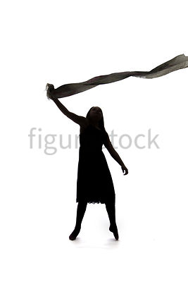 A Figurestock image of a girl in silhouette, standing, holding a scarf in the wind – shot from mid level.