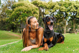 Female with long brown hair lying on grass beside Doberman with both looking into the distance