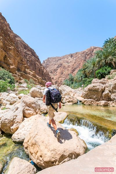 Oman, Wadi Shab. Trekker che cammina all'interno del canyon
