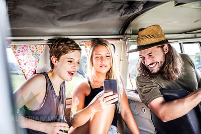 Happy friends inside van looking at smartphone