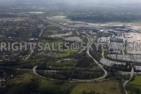 Manchester high level aerial view of M56 motorway junction 5 looking towards Business Parks and car parking and Manchester Ai...