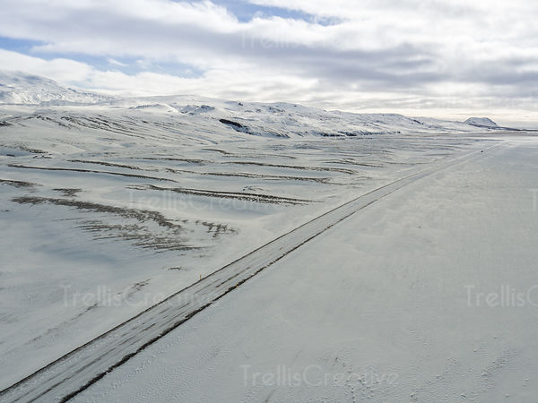 Aerial view of a long icy road in the middle of the arctic Iceland