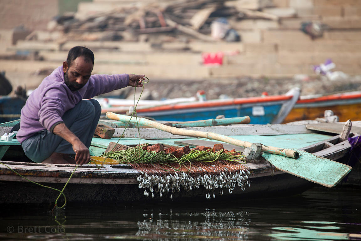 A fisherman prepares a series of interconnected, weighted hooks on his boat on the Ganges River, Varanasi, India.