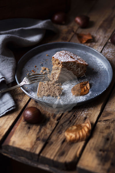 A slice of chestnut cake on rustic table