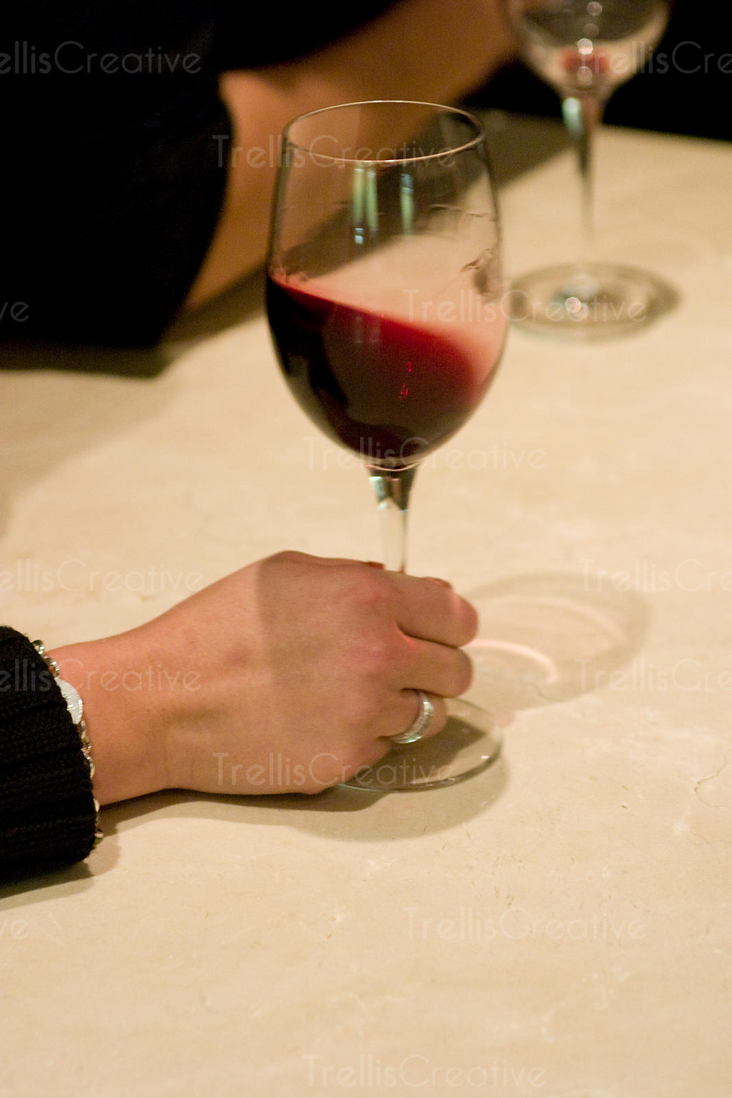 Close-up of a young woman's hand swirling a glass of red wine