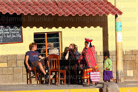Quechua woman and girl walking past tourists sitting outside cafe, Ollantaytambo, Sacred Valley, Peru