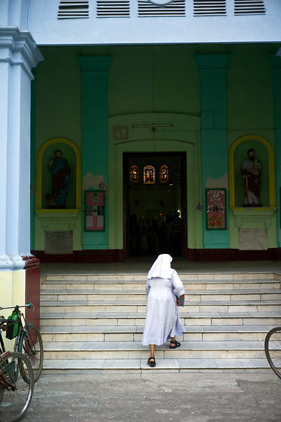 India - Chandannagar - A nun walks up the steps of the cathedral
