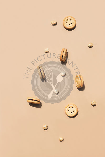 Round walnut cookies on a caramel coloured background.