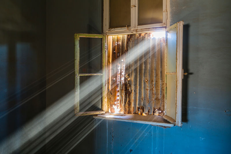 Sunbeams Shining Through Window of Abandoned House