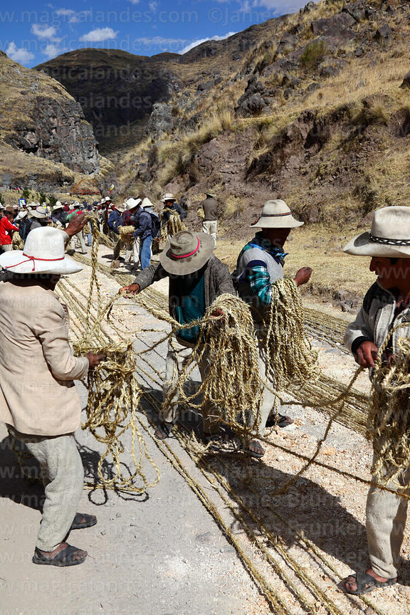 Men laying out the thin grass ropes prior to making the thicker ropes for rebuilding the bridge, Q'eswachaka , Canas province...