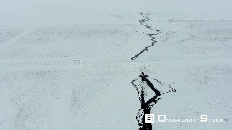A River Running Through a Snowy Lava Field in Iceland From the Air