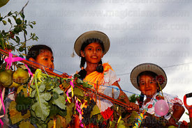 Girls wearing traditional dress on the back of a truck during Carnival parades, San Lorenzo, Tarija Department, Bolivia