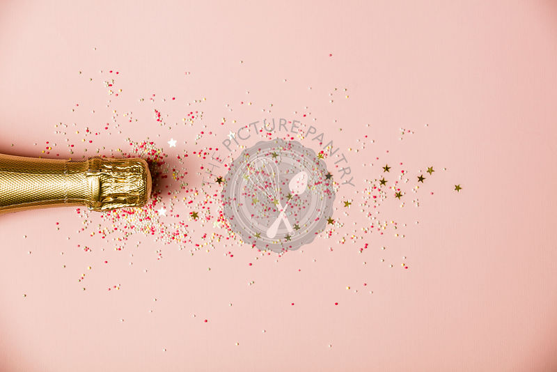 Flat lay of Celebration. Champagne bottle with ice cream sprinkles and golden star sprinkles  on pink background. Top view